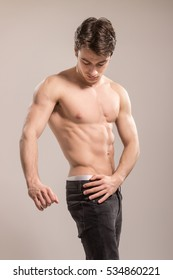 Young adult man, fit slim bodybuilder, strong core abs chest arms sideways. Wearing jeans, background studio.