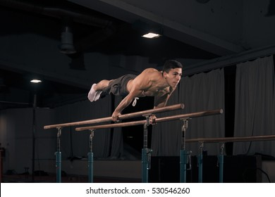 young adult man gymnast in air, holding gymnastic rings. Indoors, dark hall, gymnastics equipment.