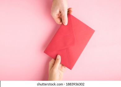 Young adult man hand giving red envelope to woman hand on light pink table background. Closeup. Pastel color.
