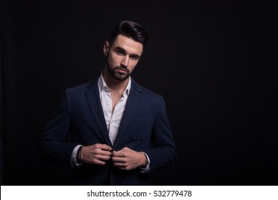 Young adult man, handsome fashion model, good looking, looking sharp. Looking at camera. Wearing suit, white shirt. Black background, studio. Upper body shot.