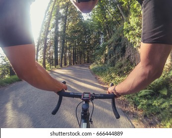 Young adult man having fun on a racing bicycle on a mountain road at sunset. POV
