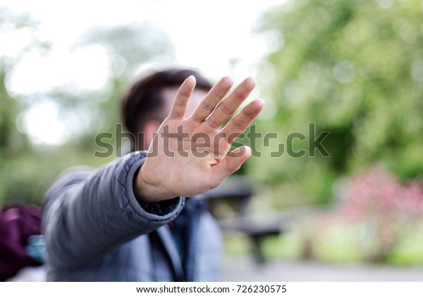 Young adult man, hipster looking, pulled out the hand hides in front of the camera. Horizontal day light close up portrait.