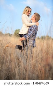 Young adult man holding his girlfriend up in tall grass