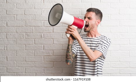 Young adult man holding megaphone annoyed and frustrated shouting with anger, crazy and yelling with raised hand, anger concept