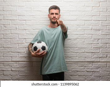 Young adult man holding soccer ball standing over white brick wall pointing with finger to the camera and to you, hand sign, positive and confident gesture from the front