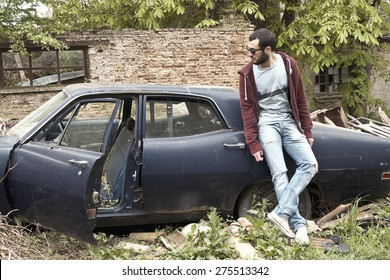 Young adult man leaning on an abandoned car