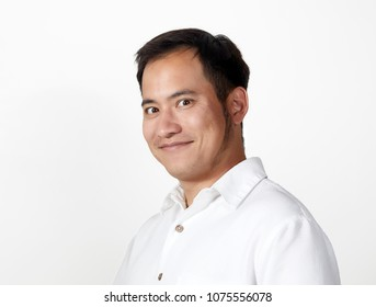 Young Adult man looking at the camera with a happy expression, wearing a white shirt isolated on white
