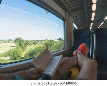 Young adult man lying on the seat of a passenger train and enjoying a trip. Wanderlust concept.