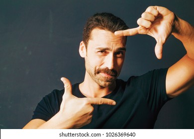 Young adult man with moustache framing his face with his hands. Handsome bearded man wearing a black t-shirt, isolated on dark background. Close up.
