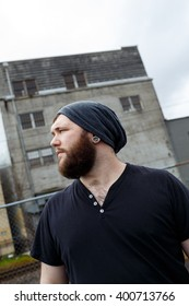 Young adult man outdoors in an urban environment for a lifestyle portrait of a bearded hipster.