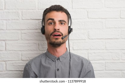 Young adult man over brick wall working as operator scared in shock with a surprise face, afraid and excited with fear expression