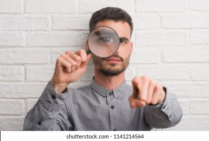 Young adult man over brick wall using magnifying glass pointing with finger to the camera and to you, hand sign, positive and confident gesture from the front