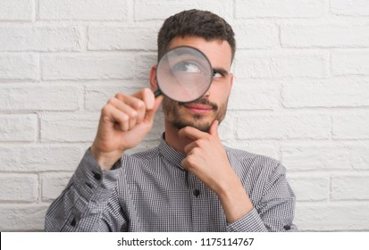 Young adult man over brick wall using magnifying glass serious face thinking about question, very confused idea