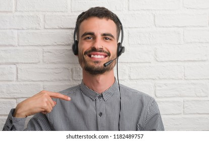 Young adult man over brick wall working as operator with surprise face pointing finger to himself
