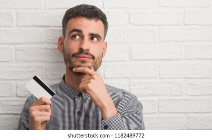 Young adult man over brick wall holding credit card serious face thinking about question, very confused idea