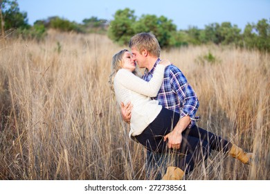 Young adult man playfully picking up his blonde girlfriend for a kiss amongst tall grass
