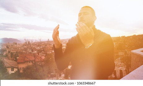 Young adult man praying outdoor with hands up in the air dua pose. Islam dua concept. Dua hands rise up. Praying to Allah.