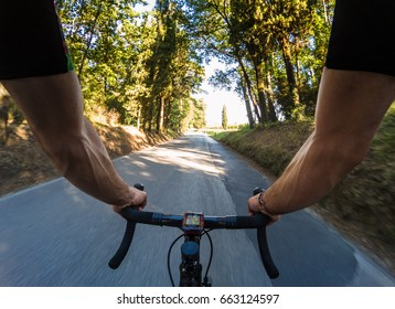 Young adult man riding a bicycle on the beautiful Chianti region countryside during summer season. POV