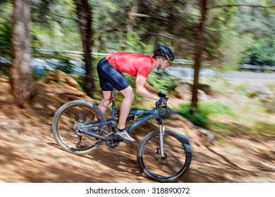 Young adult man riding a bike extreme downhill in nature