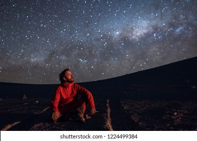 A young adult man seating and looking at the view of our Milky Way galactic core located in the constellation of Sagittarius, an amazing view at Atacama Desert. Chile