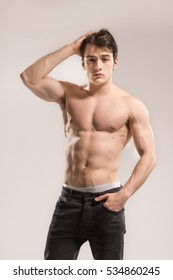 Young adult man, sexy muscular fit, posing, looking at camera. Background, studio.Background, studio.
