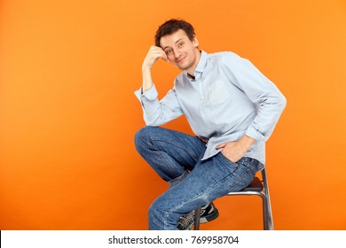 Young adult man sit on chair, touching head, looking at camera and toothy smile. Studio shot, orange background