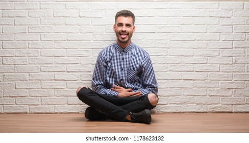 Young adult man sitting over white brick wall sticking tongue out happy with funny expression. Emotion concept.