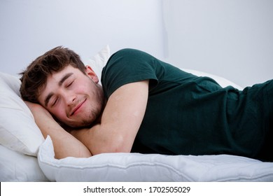 A young adult man sleeping in his clothes on top of a bed