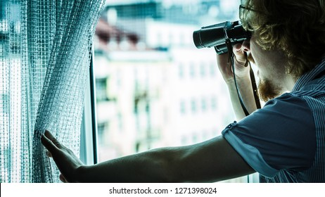 Young adult man spying at his neighbors, guy using binoculars looking through window.