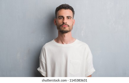 Young adult man standing over grey grunge wall with a confident expression on smart face thinking serious