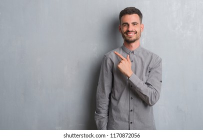 Young adult man standing over grey grunge wall cheerful with a smile of face pointing with hand and finger up to the side with happy and natural expression on face looking at the camera.