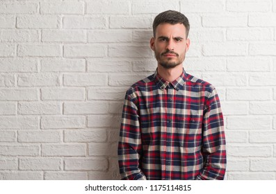 Young adult man standing over white brick wall skeptic and nervous, frowning upset because of problem. Negative person.