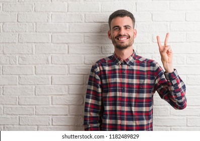 Young adult man standing over white brick wall showing and pointing up with fingers number two while smiling confident and happy.