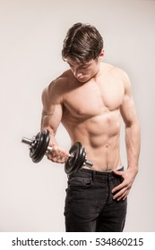 Young adult man, strong muscular, bodybuilder posing. Holding one dumbbell arm. Studio background.