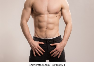 Young adult man, strong muscular, upper body shot. Wearing jeans, no head, face visible, unrecognizable person.