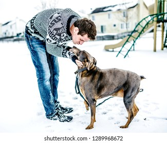 A young adult man taking is dog out to the playground, bending down towards his friend for a loving kiss and nuzzle.