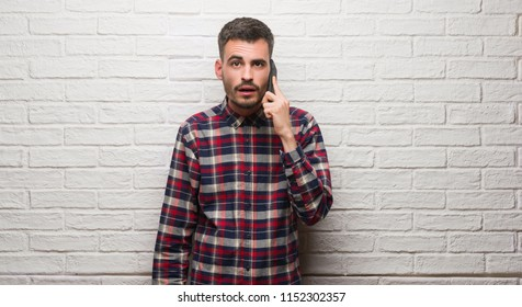 c05f16f9 Young adult man talking on the phone standing over white brick wall scared  in shock with