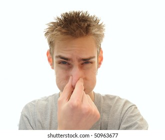 Young adult man tightly holds his hand over his nose in order to plug out the horrible odor he is smelling. Isolated on white background with room for your copyspace text.