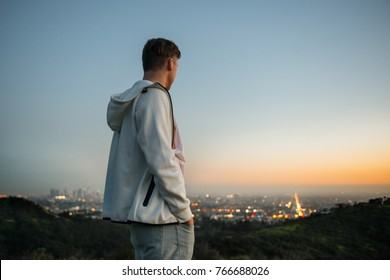 Young adult man traveling in watching the city sunset at Hollywood Hills in Los Angeles