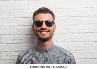 Young adult man wearing sunglasses standing over white brick wall with a happy face standing and smiling with a confident smile showing teeth