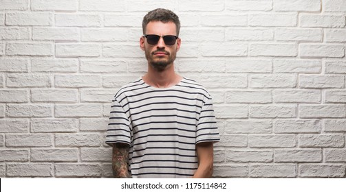 Young adult man wearing sunglasses standing over white brick wall skeptic and nervous, frowning upset because of problem. Negative person.