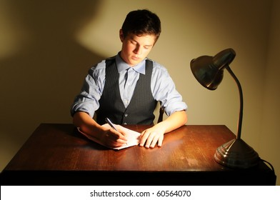 A young adult man writing a letter on a desk with a lamp.