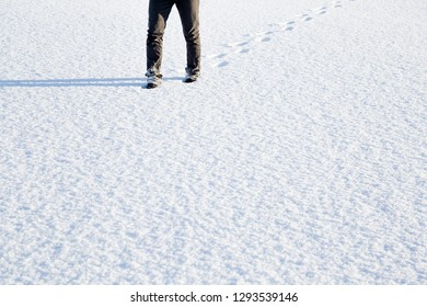 Young, adult man's legs in black boots walking on white, fresh snow. Footprints behind human. Enjoying stroll in sunny, chilly winter day. Empty place for text, quote or sayings.