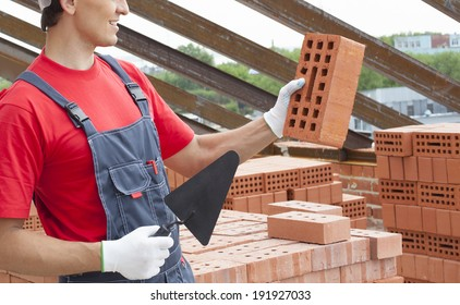 Young adult mason wearing overall holding brick and trowel on metal beam roof and sky background Unrecognizable person in blue and red uniform on brick stack backdrop No face