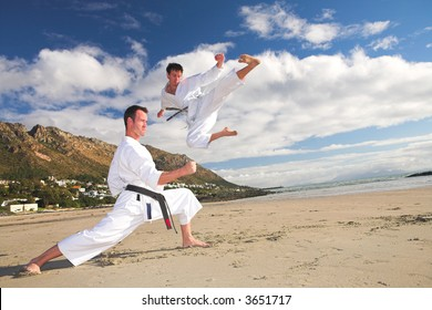 Young adult men with black belt practicing on the beach on a sunny day. The man doing the flying kick in the background has movement. Focus on the standing man