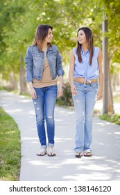 Young Adult Mixed Race Twin Sisters Walking Together Outside.