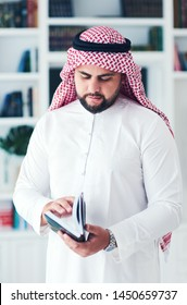 young adult muslim man reading book indoors