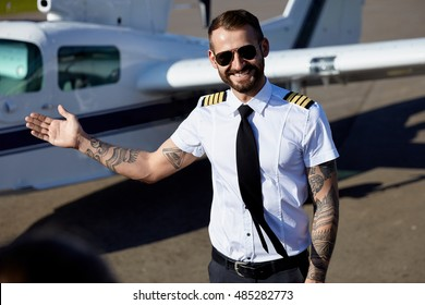 Young adult pilot with tattoos wearing uniform welcomes you to fly on his air plane