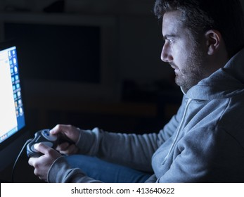 Young adult playing with video-game during night