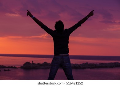 Young adult raising arms to the sea at sunset hands up